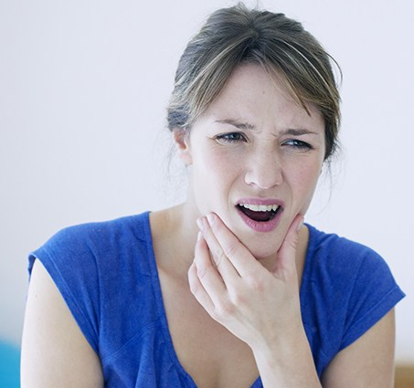 Woman in need of T M J therapy holding jaw in pain