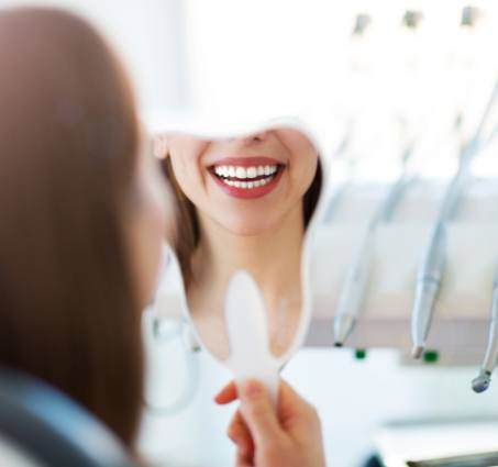 Woman looking at her smile after restorative dentistry