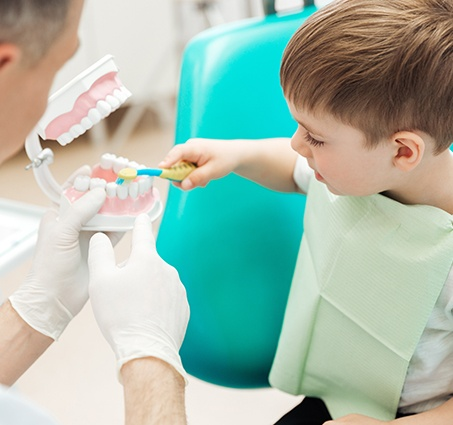 Dentist helping young boy practice toothbrushing at children's dentistry visit