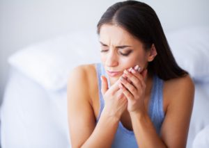 woman suffering toothache in Muskegon